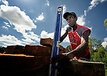 A man checks the plumb of a wall during the construction of a school in Karonga, a town in northern Malawi which was hard hit by 2009 earthquakes. The ACT Alliance is helping residents of this community rebuild their homes and lives after the quake.
