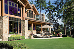 an open patio with an umbrella covering a dining table and six outdoor chairs sits in front of a large, lodge like estate sized home under a summer blue sky with a lawn of perfectly manicured green grass, colorful summer pots on the patio, and mature evergreen trees behind
