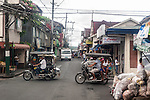 """Tricycles for hire dart across the street in front of """"my"""" jeepney to Sampaloc on a misty early morning in Lucban, Quezon Province, the Philippines."""