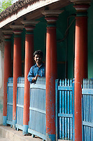 Man at veranda railing. Thittacheri. South India.