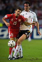 Christoph Metzelder of Germany fouls Ebi Smolarek of Poland at FIFA World Cup Stadium, Dortmund, Germany, June 14, 2006. He received a yellow card for this play.