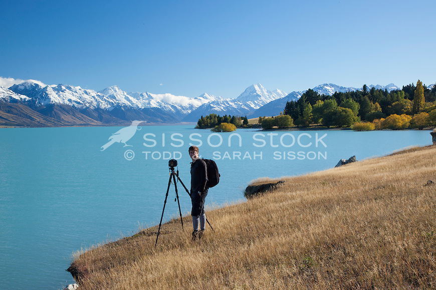Landscape photographer at work on the shores of Lake Pukaki with Mt Cook and southern alps in background.