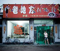 A woman stands outside a cafe on the Taiyuan-Linfen highway.