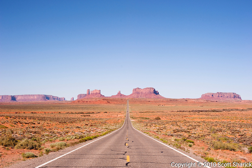 A long straight road crosses the desert landscape with buttes in the distance. Missoula Photographer