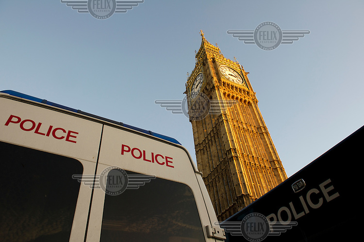 Police vans parked on Westminster Bridge beneath the Houses of Parliament and the Big Ben clock tower in London during during a demonstration by students against the government's proposed increase in university tuition fees.