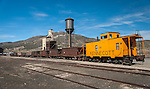 Caboose and abandoned railroad cars in the East Ely Yard of the Nevada Northern Railway National Historic Landmark site with the Coal and Water Tower