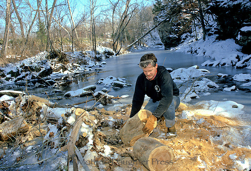 Man with log being cut for firewood on snow covered creek