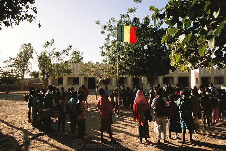 Raising the flag before school in the village of Kouakourou, Mali. Children, Child, Africa. From coverage of revisit to Material World Project family in Mali, 2001.