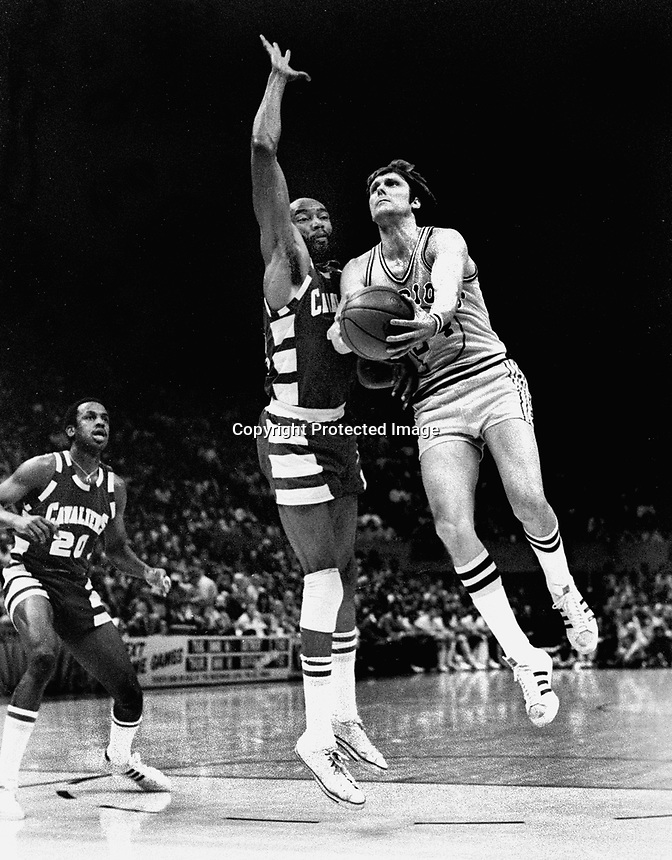Golden State Warrior Rick Barry goes against former teamate Nate Thurmond of the Cleveland Cavaliers.(1976 photo by Ron Riesterer)