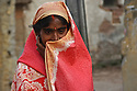A woman appears shy towards the camera along the streets of Varanasi, India