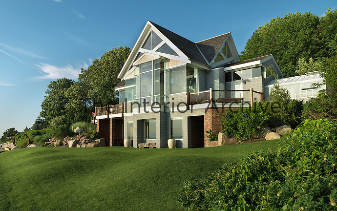 The house is set into the landscape with decks extending from both sides and the lawn sweeps down to the beach