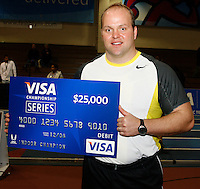 Adam Nelson with his $25,000 check after winning the VISA CHAMPIONSHIP SERIES for the 2008 Indoor Season. Photo by Errol Anderson,The Sporting Image.