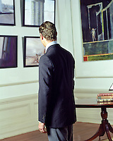 back of a man looking at art work hanging on a wall
