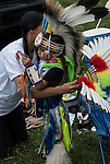 Native American , Chaske Hill Sicangu Lakota and Seneca , mother dressing and preparing her 3 year old son as he looks in the mirror before the pow wow dance contest at the Thunderbird powwow in Queens, NY .