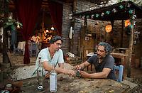 "Guillermo ""Willy"" Olguin shares a mezcal with friend Marco Tufi. Jardin Cebu at Guillermo Olguin´s studio. Oaxaca, Oaxaca"
