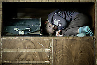 Young boy crouching in a worn wooden cupboard, making eyecontact with the camera. Beside him is an old typewriter.
