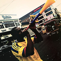 A Colombian football fan plays a vuvuzela on the street of Cali, Colombia, 24 June 2014.