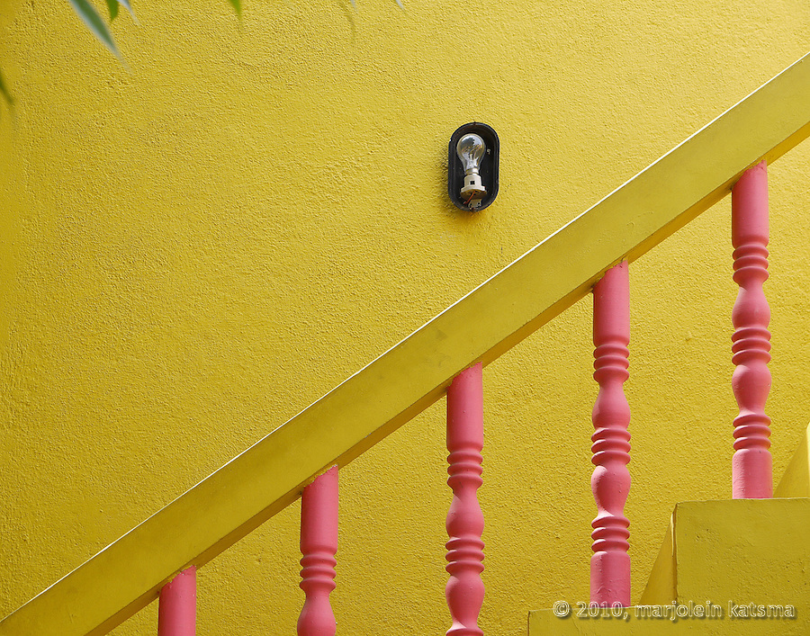 A close-up of a house in Mamallapuram (Tamil Nadu, India): a  perfect example of the bright colors we often see houses and walls painted in in South India. And often something is a little bit messy, or a little bit broken, like the lamp on this wall.