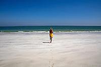 A woman walks along a deserted beach towards the sea