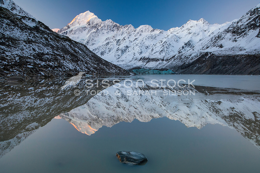Aoraki Mt Cook & the Southern Alps reflected in Hooker Lake, early winter.  Aoraki Mt Cook National Park, NZ.