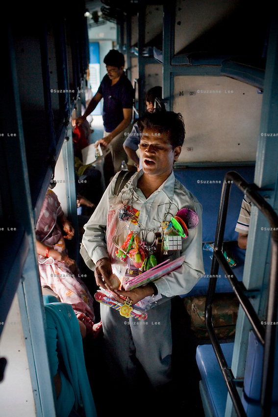 A blind man sells his ware, ranging from travel padlocks and chains to board games and toiletries, to train passengers on the Himsagar Express 6318 as it passes through Maharashtra on 8th July 2009.. .6318 / Himsagar Express, India's longest single train journey, spanning 3720 kms, going from the mountains (Hima) to the seas (Sagar), from Jammu and Kashmir state of the Indian Himalayas to Kanyakumari, which is the southern most tip of India...Photo by Suzanne Lee / for The National