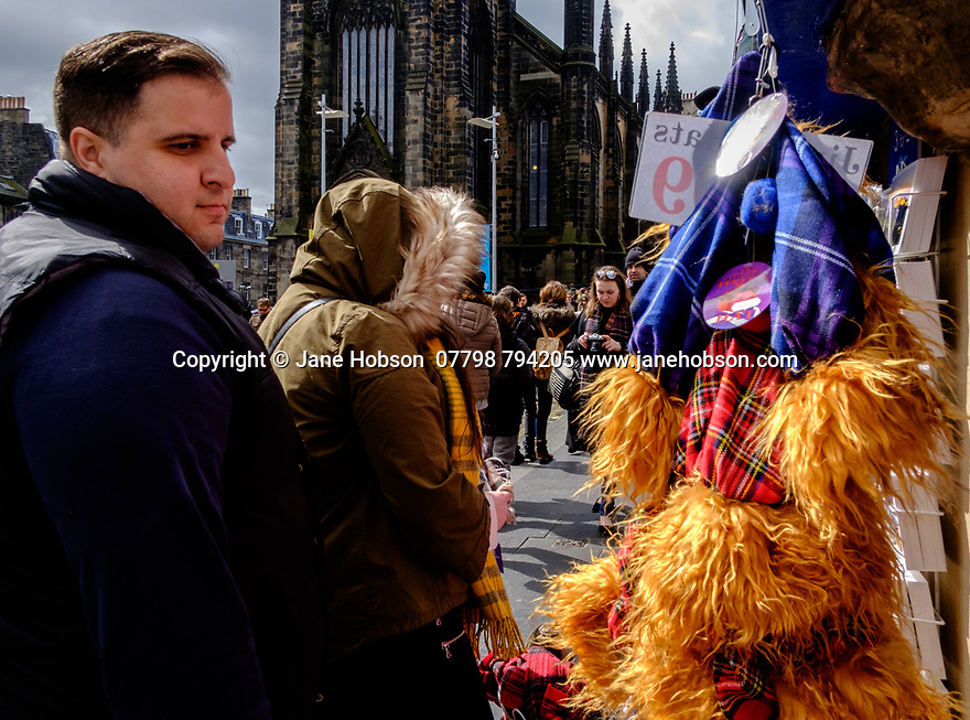 """Edinburgh, UK. 15.04.2017. A man looks at a string of """"Jimmy"""" hats, hanging outside a shop on the Royal Mile. Photograph © Jane Hobson."""