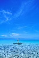 Fisherman is framed by blue in the Aitutaki Lagoon, Aitutaki, Cook Islands