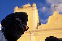 Black man at religious party, Brazil. City: Jardim do Seridó, State: Rio Grande do Norte. Festa do Espontão ( Espontao Party ), catholicism, afro-descent man, religion, yellow church, cross.