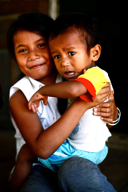 A Bahnar boy cries as his sister holds him for a photograph in a village near the Central Highlands town of Kon Tum, Vietnam. The Bahnar are one of more than two dozen hill tribes known formerly in the West as Montagnards, but who are now called the Dega. April 14, 2012.