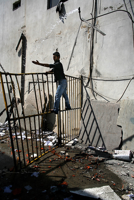 Saida, Lebanon, July 19 2006.Ali Hassan, 20, tries to get fresh water from a pipe broken in the bombardment by Israeli Air Force of a group of civilian houses and shops in the southern outskirts of Saida, near the coastal road. There was no military or strategic target in the area.