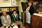 The Kings Head, High Ham, Langport, Somerset. UK Village pub 1980s. Landlady, Louisa May Brown (known as Maisie) and two locals. Note the dartboard scores in chalk on the  underside of the wooden flap leading into the bar.