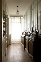 In the long corridor outside the bathroom, dozens of framed photographs and prints are displayed on antique cupboards