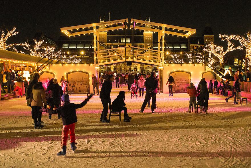 Nederland, Amsterdam, 4 jan 2015<br /> Kunstijsbaan op het Museumplein. Een leuke attractie, zeker als het mooi weer is. De hoofdsponsor van de ijsbaan heeft ook gezorgd dat elke foto die gemaakt wordt een lekker autentiek sfeervol plaatje oplevert. Vroeger kon alleen met echt strenge winters op de grachten geschaatst worden, nu lijkt het alsof het altijd kan in Amsterdam.<br /> <br /> Foto: (c) Michiel Wijnbergh
