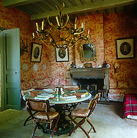 A large chandelier created from antlers creates an unusual focal point in a dining room where the walls and surrounding banquette sofas are lined in red-and-white toile de Jouy