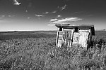 Tiny shed in remote dual environment under summer skies in long grass