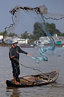 "Sa, 45, casts a net out for fish on the Hau Giang River, a tributary of the Mekong River, in Chau Doc, in the An Giang Province, Vietnam. When the Mekong River reaches Vietnam it splits into two smaller riveres. The ""Tien Giang"", which means ""upper river"" and the ""Hau Giang"", which means ""lower river"". Photo taken on Monday, December 7, 2009. Kevin German / Luceo Images"