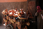 A woman stands by a cart full of pottery on a street in Marrakesh, Morocco.