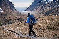 Female hiker hiking trail towards Horseid beach, Moskenesøy, Lofoten Islands, Norway