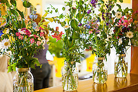 Bride preparing wedding bouquets with local flowers for country wedding