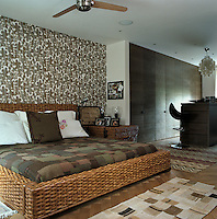 The large wicker-framed bed, patchwork quilt and floral wallpaper introduce an element of rusticity to the master bedroom