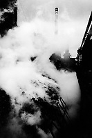 """Poland. Silesia. Chorsow. """" Hutta Kosciuszko """" is the factory's name. Coal pile and coke burning. Major polluted area due to old iron and steel works. Chorsow is a small town, distant 20 km from Katowice. © 1991 Didier Ruef .."""
