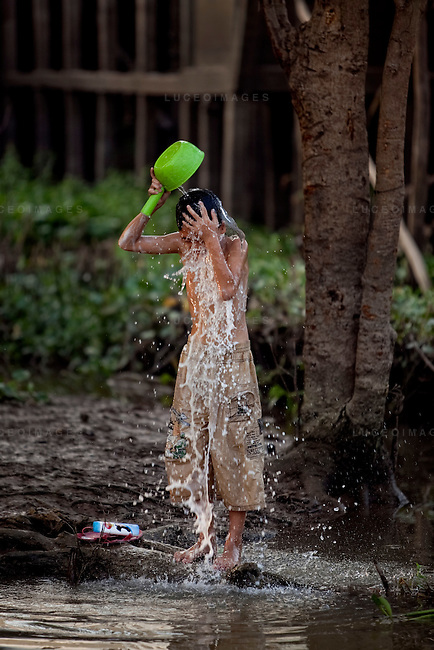 "Son, 12, bathes himself in the Hau Giang River, a tributary of the Mekong River, in Chau Doc, in the An Giang Province, Vietnam. When the Mekong River reaches Vietnam it splits into two smaller riveres. The ""Tien Giang"", which means ""upper river"" and the ""Hau Giang"", which means ""lower river"". Photo taken on Monday, December 7, 2009. Kevin German / Luceo Images"
