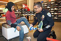 Santa Monica Police Deputy Chief  Al Venegas helps Joe Peña, 11, try on a pair of shoes during the Salvation Army Santa Monica Corps 28th Annual Sears Holiday Shopping Spree on Tuesday, November 13, 2012.