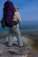 A backpacker looks out over Lake Superior from a sandstone outcropping at Mosquito Beach in Pictured Rocks National Lakeshore near Munising, Mich.