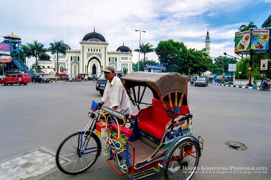 Indonesia, Sumatra. Medan. A colourful becak in front of Mesjid Raya.