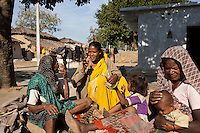 Shanti Adivasi (in yellow saree), 52, chats with villagers as she distributes this week's Khabar Lahariya newspaper in a remote tribal village in Manikpur, Chitrakoot, Uttar Pradesh, India on 6th December 2012.  Shanti used to be a wood gatherer, working with her parents since she was 3, and later carrying up to 100 kg of wood walking 12km from the dry jungle hills to her home to repack the wood which sold for 3 rupees per kg. After learning to read and write in an 8 month welfare course, at age 32, she became a reporter, joining Khabar Lahariya newspaper since its establishment in 2002, and making about 9000 rupees per month, supporting her family of 14 as the sole breadwinner. Photo by Suzanne Lee for Marie Claire France.