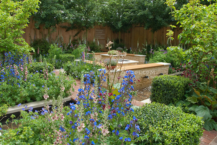 Backyard landscaping with stone walls, brick patio, lots of flowers, shrubs, trees, privacy fence wall, waterfall water feature, larkspur Verbascum, Boxwood trimmed into shapes