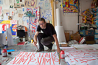 SP38, a French artist in his studio in East Berlin painting placards with the slogan &quot;Quality Street&quot;. He posts the placards on the sides of buildings as an ironic comment on the gentrification of former run-down districts of East Berlin that attracted many international artists after the fall of the Berlin Wall due to their affordable rents (or often free rents in numerous abandoned building which were squatted). Areas in East Berlin popular with artists are now becoming more expensive as trendy restaurants and galleries have followed in the artists' wake.