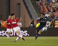 Manchester United FC midfielder Ji-Sung Park (13) takes a shot as New England Revolution midfielder Ryan Guy (13) defends. In a Herbalife World Football Challenge 2011 friendly match, Manchester United FC defeated the New England Revolution, 4-1, at Gillette Stadium on July 13, 2011.