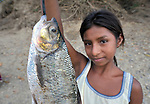 A girl displays a fish she caught in the Salinas River in Santa Elena, Guatemala.